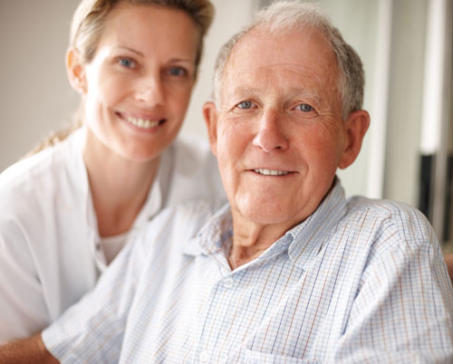 Elderly man with young woman in background