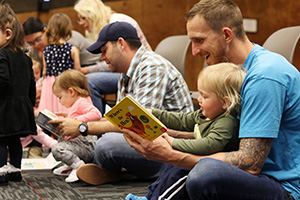 Dads reading books to young toddlers